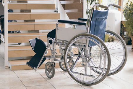 invalidity: Empty wheelchair and stairs. Disabled accessibility reality.