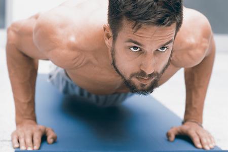 soustředění: Síla a motivace. Mladý hezký muž dělá push-up v tělocvičně