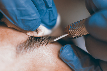 cosmetologist: Permanent make up. Cosmetologist applying permanent makeup on eyebrows.