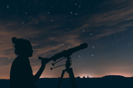 Woman with astronomical telescope. Night sky, with clouds and constellations, Hercules, Draco, Ursa Major, Ursa Minor, Big Dipper, Botes Stock Photo