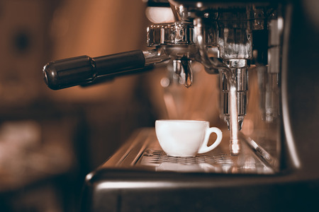 Coffee espresso. Espresso machine making coffee, golden espresso flowing.
