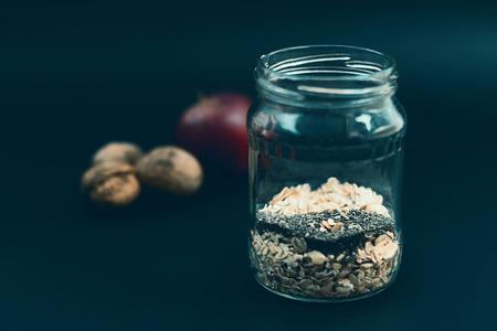 avena: Healthy breakfast with chia seeds. Apple nut overnight oats and chia, in glass jar. Preparation overnight breakfast with flakes of oats, chia, apple, nuts. Foto de archivo