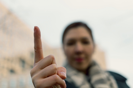 Angry woman warning you. Blurred  woman wagging her finger. Attention, listen to me. Close up finger of young woman.