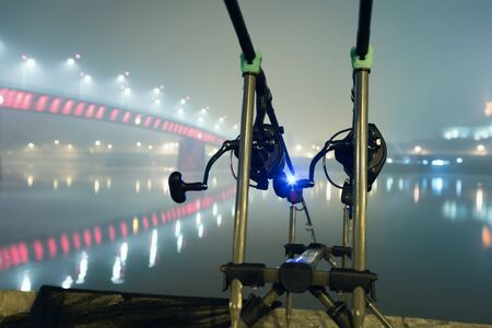 Carp spinning reel angling rods in foggy night. Urban Edition. Night Fishing, Carp Rods, City lights. Foggy night.