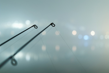 spinning reel: Carp spinning reel angling rods in foggy night. Urban Edition. Night Fishing, Carp Rods, City lights. Foggy night.