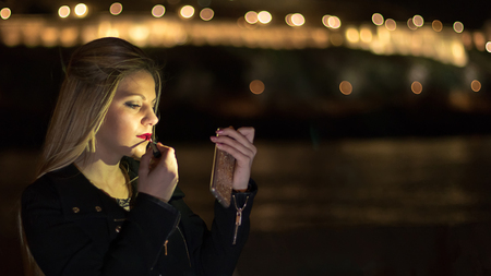 Cute young girl putting lipstick on looking at Smartphone, Night lights bokeh.