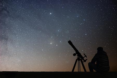 Man with astronomy  telescope looking at the stars. Man telescope and starry sky. Night sky. Milky way galaxy. Archivio Fotografico