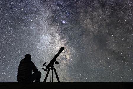 Homem com o telescópio da astronomia que olha as estrelas. Telescópio de homem e céu estrelado. Céu noturno. Galáxia Via Láctea.