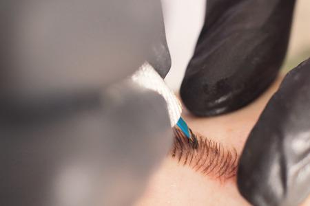 Cosmetologist die permanente make-up op wenkbrauwen toepast. Permanente tatoeëren van wenkbrauwen. Stockfoto - 76092985