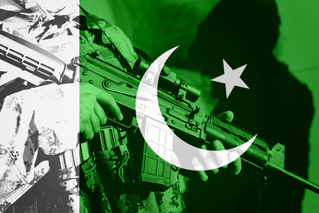 Soldier with machine gun with national flag of Pakistan