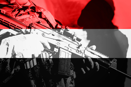 Soldier with machine gun with national flag of Yemen