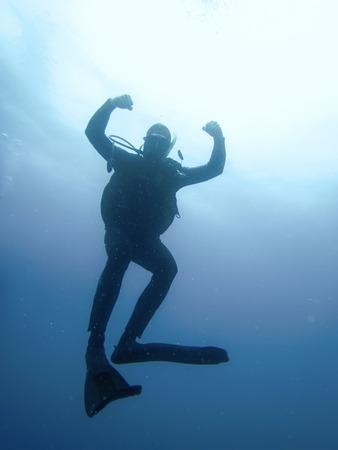 太陽に対してスキューバ ダイバー水中シルエット 写真素材
