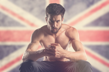 Muscular man with Union Jack Flag behind Banque d'images