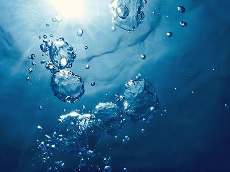 Burbujas submarinas luz del sol a través de la superficie del agua. Fondo bajo el agua. Foto de archivo