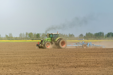Farmer in tractor preparing land seedbed cultivator. Agriculture tractor landscape. Stock Photo
