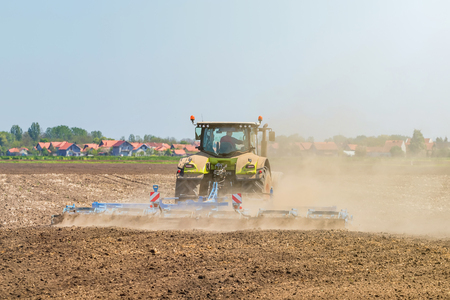 Farmer in tractor preparing land seedbed cultivator. Agriculture tractor landscape. 写真素材