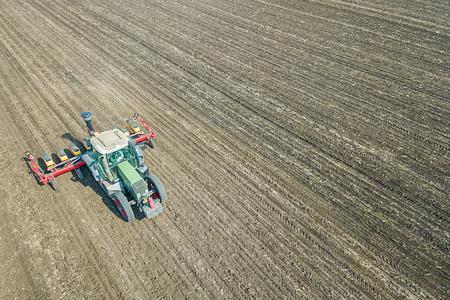 Farmer seeding crops at field. Seeding Aerial View.