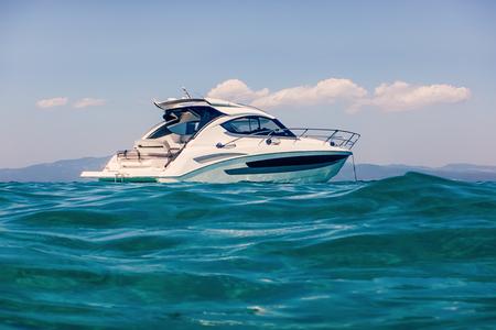 Barca a motore che galleggia sulle acque turchesi chiare