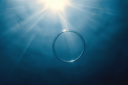 Bubble ring Underwater ascends towards the sun. Imagens