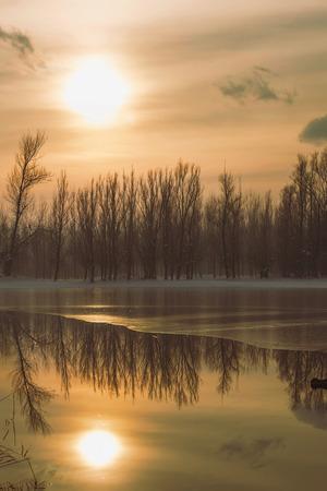 Frozen lake in forest sun reflection, winter reflection landscape Stock Photo