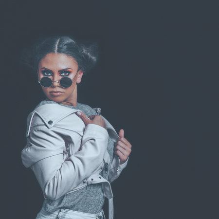 Fashion Girl Posing, wearing Urban Hipster Style, Sweet Pastel Colors, Trendy Sunglasses, Pink Jacket, Dark Background.