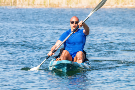 Young Man Kayaking on Lake. Lake Kayaking. Stock Photo