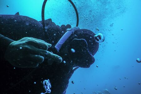 Scuba diver flipping off underwater, Middle finger Underwater Imagens