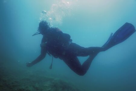 Scuba Diver Swimming Underwater Explores Reef and Examines Seabed