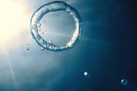 Bubble ring Underwater ascends towards the sun. Reklamní fotografie