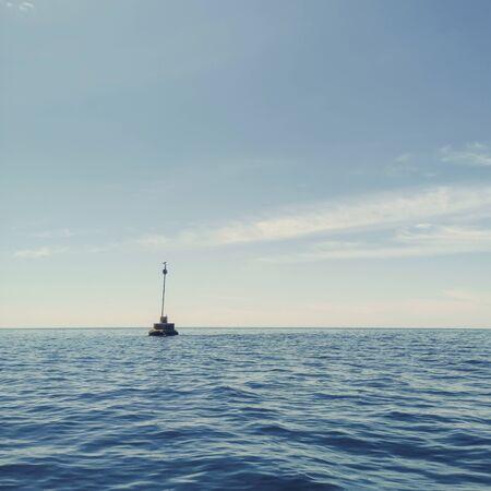 Small Lighthouse on the Horizon Blue Sky Banco de Imagens