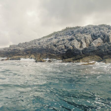 Sea Landscape Waves Crashing against the Rocky Shoreline, Cloudy Sky