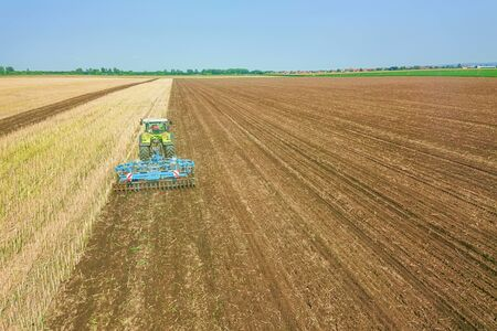 Tractor at work, cultivating a field, Seedbed cultivator Aerial View. Stok Fotoğraf