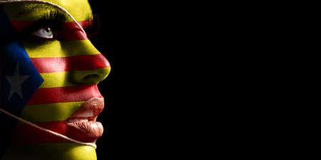 Catalonia flag painted on a face of a young woman, national flagon face
