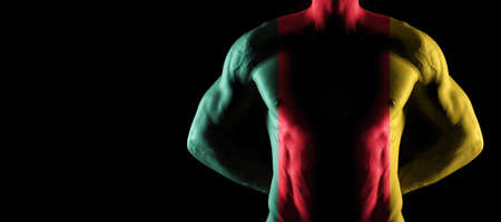 Cameroon flag on muscled male torso with abs, black background
