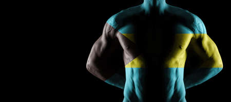 Bahamas flag on muscled male torso with abs, black background