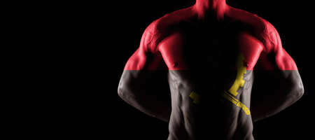 Angola flag on muscled male torso with abs, black background
