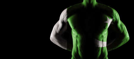 Pakistan flag on muscled male torso with abs, black background