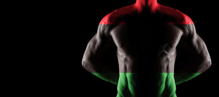 Libya flag on muscled male torso with abs, black background