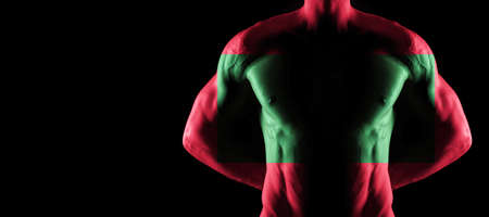 Maldives flag on muscled male torso with abs, black background Archivio Fotografico