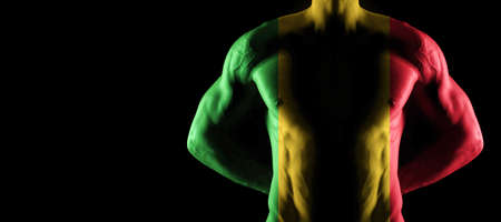 Mali flag on muscled male torso with abs, black background Archivio Fotografico