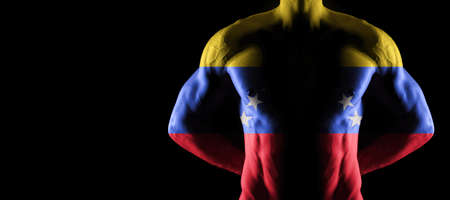 Venezuela flag on muscled male torso with abs, black background Archivio Fotografico