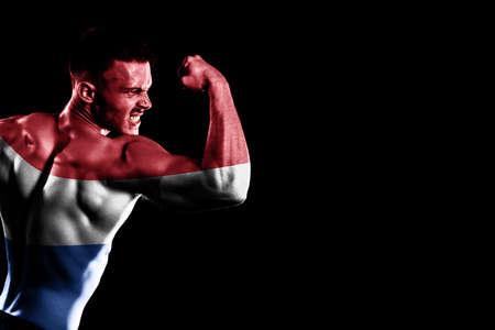 Netherlands flag on handsome young muscular man black background Banco de Imagens