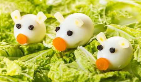 Children food, little pigs of quail eggs with lettuce