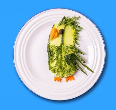 Art food, parrot from vegetables in a plate on a blue background