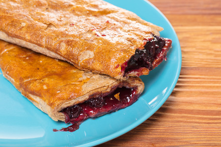 strudel: Baking, cherry strudel in a plate on wooden background