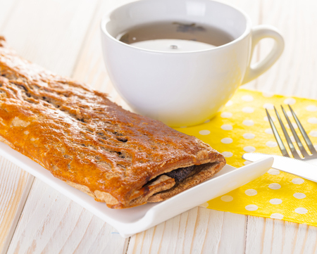 strudel: Baking strudel with poppy seeds and tea on a wooden white background Stock Photo