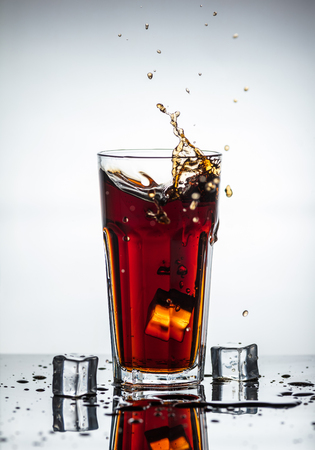 humid: Splashes of drink from a glass with ice cubes Stock Photo