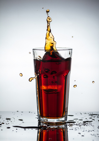 Splashes of drink from a glass with ice cubes Stock Photo