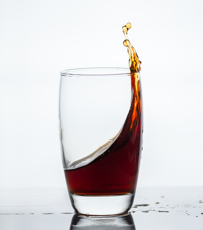 splash of drink from a glass with reflection Stock Photo