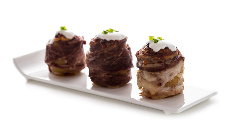 potato wrapped in bacon baked with cheese on white background